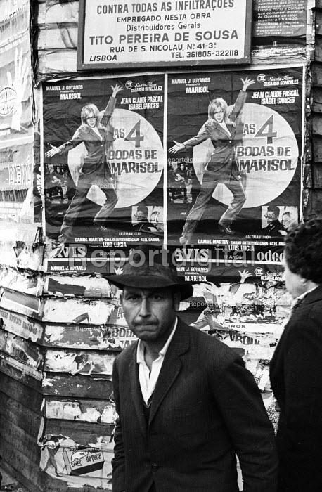Street scene in Lisbon, Portugal. Man with a movie poster for the film Las 4 bodas de Marisol, 1968. - Romano Cagnoni - 1968-03-06