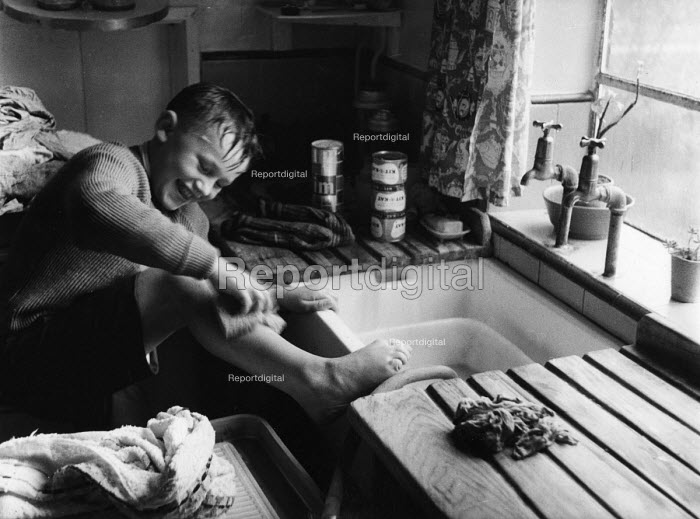 Polish refugee child washing his legs in the kitchen sink at his home in west London in the late 1950s - Roger Mayne - 1958-02-15