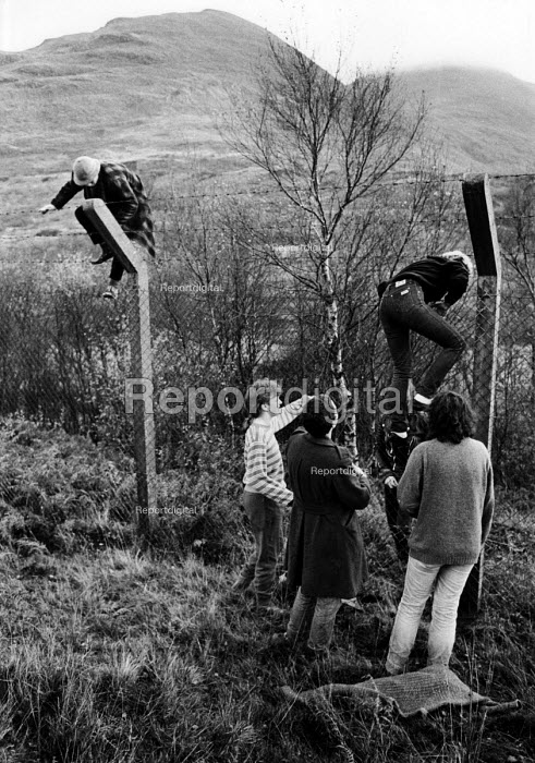 Members of Faslane Peace Camp in Scotland take non-violent direct action by entering Glen Douglas armaments depot- a NATO defence munitions depot- by climbing over the security fence to plant flower bulbs for peace. - Rick Matthews - 1983-03-14