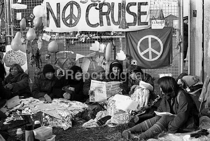 Women at the Greenham Common Peace Camp in Newbury, Berkshire, reading a story in the Daily Mail about their protest against US air bases hosting nuclear weapons in the UK whilst blockading a gate. - Stefano Cagnoni - 1982-12-13