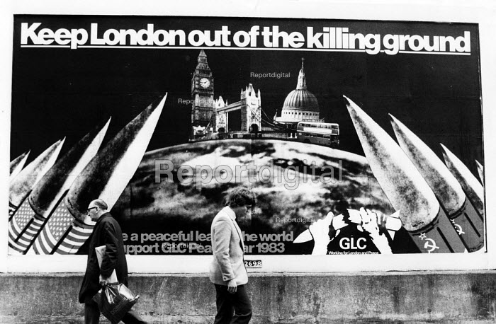 GLC peace poster on the streets of London at the height of the Cold War between the USA and the USSR. A photomontage by Peter Kennard on nuclur weapons and mutually assured destruction or MAD- a doctrine of military strategy and national security policy in which a full scale use of high-yield weapons of mass destruction by two or more opposing sides would cause the complete annihilation of both the attacker and the defender. It is based on the theory of deterrence where the threat of using strong weapons against the enemy prevents the enemys use of those same weapons. In this case the Cold War stand off between Russia (USSR) and the west - Stefano Cagnoni - 1983-03-01