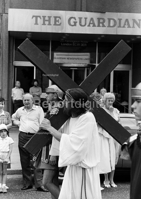 London Procession in Honour of Our Lady of Mount Carmel: A figure dressed as Jesus and carrying a wooden cross passes the Guardian Newspaper building during the annual Italian religious procession through Clerkenwell, London - Stefano Cagnoni - 1989-07-15