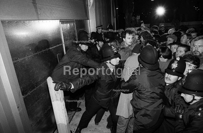 Stockport Messenger Police officers grapple with trade union members at a mass picket in support of NGA members on strike in a dispute with Eddie Shahs Messenger Newspaper Group over his use of non-union scab workers to typeset MNG publications Warrington, Lancashire, 1983. - John Smith - 1983-11-29