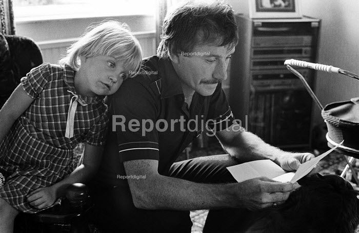 Great Houghton, near Doncaster: striking miner at home reading a letter from the DHSS refusing help, watched by his young daughter. Benefit was withdrawn. - John Smith - 1984-08-03