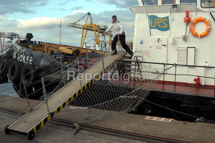 Sean Draper, chaplains assistant at Mersey Mission to Seafarers, leaving a tugboat in Liverpools port after visiting its crew to cheak on their welfare. - Rob Bremner - 2004-03-23