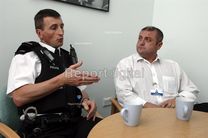 Police constable Chris Brown who is a community safety officer in the Bootle area of Merseyside. Chris is talking to a housing officer in the area about the problems. - Rob Bremner - 2006-11-11