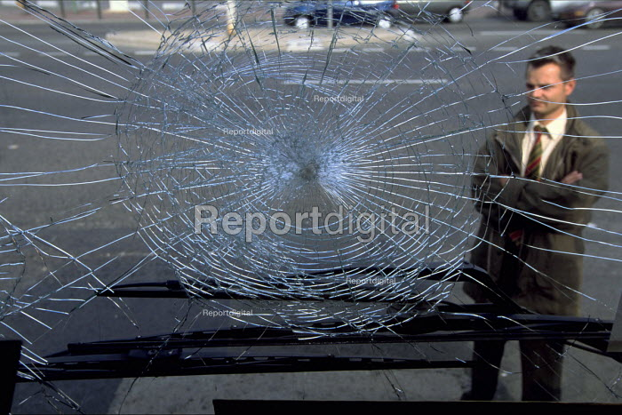 A Bus driver with the broken windscreen of a bus after an attack inwhich paving stones were thrown breaking the glass. Burden, France. - Marta NASCIMENTO - 1998-09-24