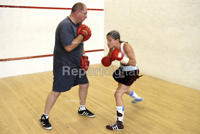 Trainer, Peter Coulter, sparring with the boxer, Shanee Martin, before a fight for the British Masters Female Super Flyweight Title, At Goresbrook Leisure Centre in Dagenham, London. - Rogan Macdonald - 2006-07-23