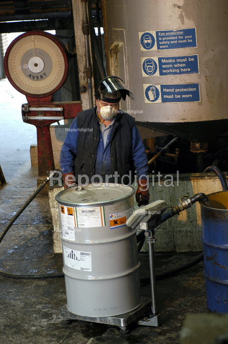 A worker tips 25 kg bags of resin nto a vessel of kerosene... - Ray Smith, RS408009.jpg