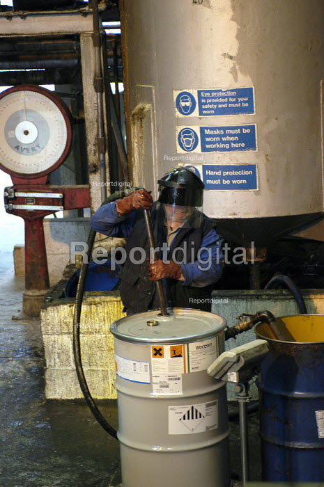 A worker pumps out a solution of tributyltin naphthenate in white spirit from a 200 litre drum into a vat of kerosene in the manufacture of pesticides, Newcastle upon Tyne. - Ray Smith - 2003-05-16