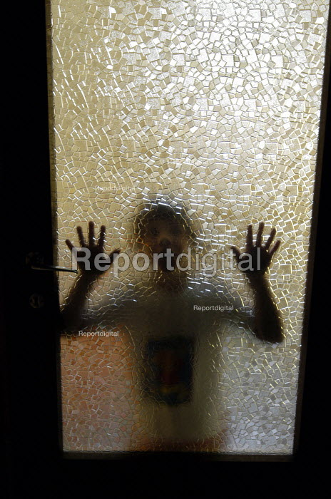 Child leaning against glass door having locked herself in... - Stefano Cagnoni, SC03BAGN.jpg