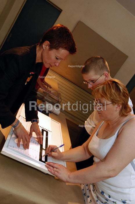 French voter signs her name in the electoral register to acknowledge that she has voted at the Town Hall polling station of Le Blanc Mesnil, a northern suburb of Paris, in the national referendum on the European Constitution. The final outcome by a clear majority was Non. - Stefano Cagnoni - 2005-05-29