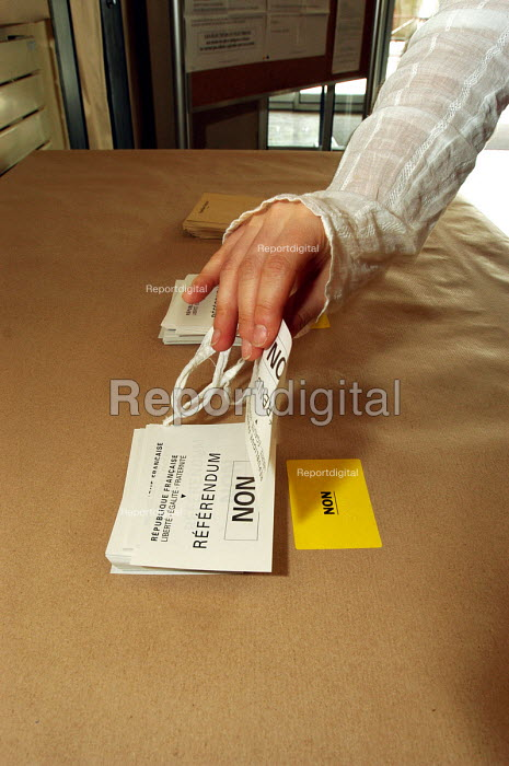 Voter taking a voting paper marked Non in the Town Hall polling station of Le Blanc -Mesnil, a northern suburb of Paris, in the national referendum on the European Constitution. The final outcome by a clear majority was Non. - Stefano Cagnoni - 2005-05-29
