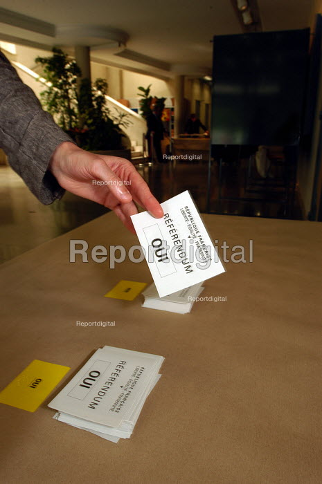 Voter taking a voting paper marked Oui in the Town Hall polling station of Le Blanc -Mesnil, a northern suburb of Paris, in the national referendum on the European Constitution. The final outcome by a clear majority was Non. - Stefano Cagnoni - 2005-05-29