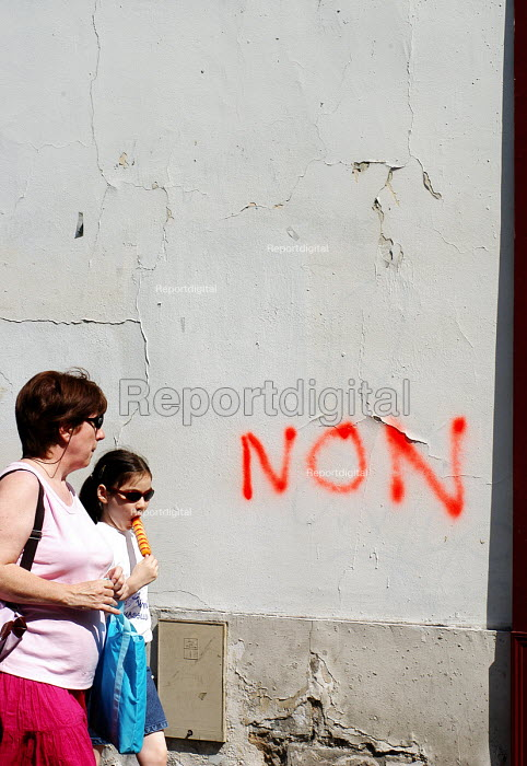 Mother and daughter walking in Parisian street with graffiti urging voters to Vote No in the national referendum on the European Constitution. The final outcome by a clear majority was Non. - Stefano Cagnoni - 2005-05-28
