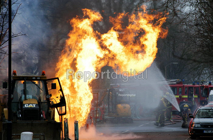 Firefighters carefully approach a blaze caused by a JCB digger fracturing a gas pipe whilst digging the road - Stefano Cagnoni - 2005-01-30