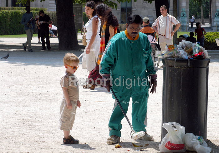 Young boy watching as street cleaner picks up litter strewn in a park - Stefano Cagnoni - 2005-05-28