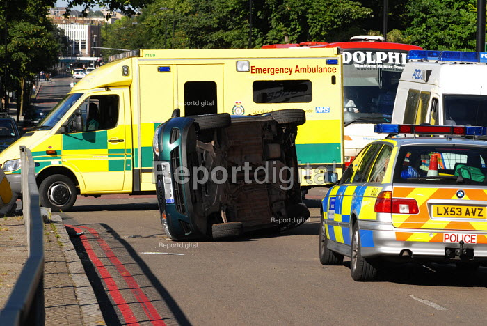 Police and ambulance at the scene of a overturned car involved in an accident at a blackspot junction in Holloway, north London. In the past 3 years 17 collisions have occurred at this junction, one involving the death of 2 people. - Stefano Cagnoni - 2006-07-14