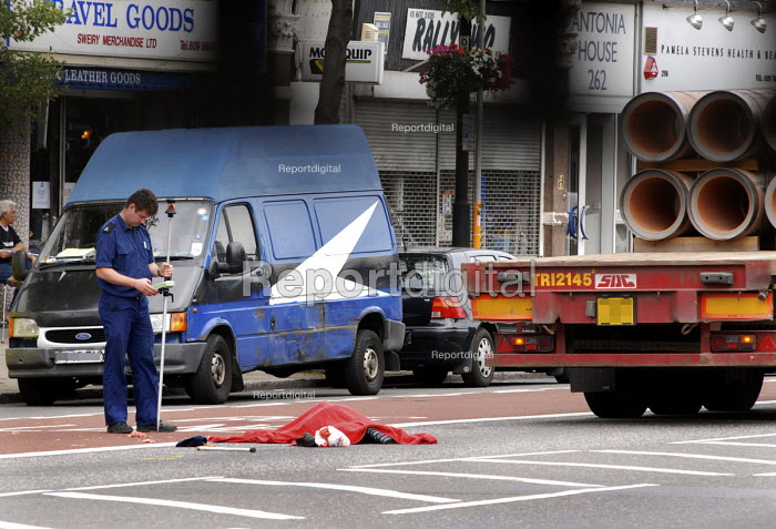 Police Officer takes measurements at the scene of a road fatality on Holloway Road in north London. The victim ws killed as he crossed this busy arterial route by the HGV seen in the background - Stefano Cagnoni - 2006-07-13