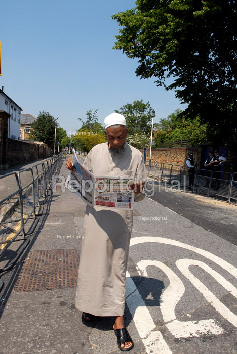 Elderly British Muslim reading an Arabic newspaper within a police cordon whilst waiting for the start of a protest opposite Forest Gate Police Station against British Muslims perceived sense of persecution following recent police raids on a Muslim home allegedly in search of chemical weapons. - Stefano Cagnoni - 2006-06-09