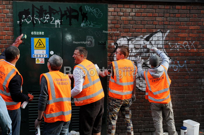 Offenders wearing tabards with Community Payback on their backs clean up graffiti on walls in East London - Stefano Cagnoni - 2009-06-09