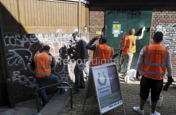 Offenders wearing tabards with Community Payback on their backs being filmed by news tv crew as they clean up graffiti on walls in East London - Stefano Cagnoni - 2009-06-09