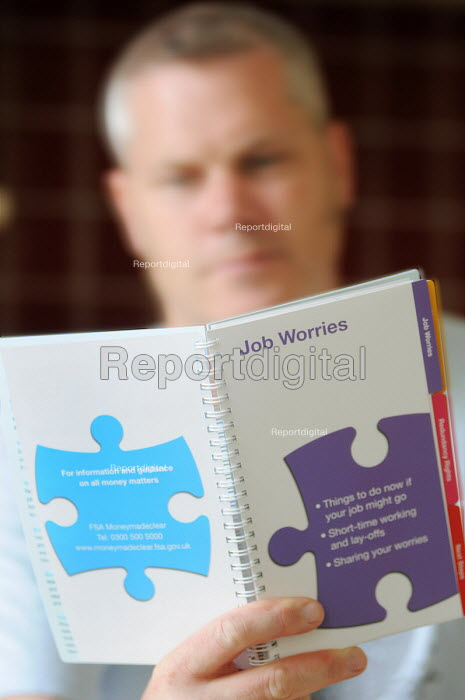 Man in his mid-forties who has been made redundant reading about his redundancy rights in an advice booklet produced by the Financial Services Authority (FSA) - Stefano Cagnoni - 2010-07-01