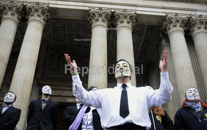 Occupy LSX at St Paul's Cathedral. The protestors, some in masks, wave their hands in support of words from the Bishop of London, the Reverend Richard Chartres, as he addresses the crowd at St Pauls as part of a dialogue between the Church and the protestors. - Stefano Cagnoni - 2011-10-30
