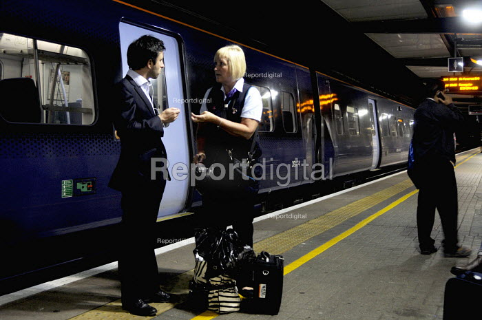 Ashford International Station in Kent: a ticket guard on a late night train into London apologizes to passengers as the train they were travelling on was cancelled, after a relief driver failed to arrive for their changeover shift due to illness. - Stefano Cagnoni - 2012-07-09