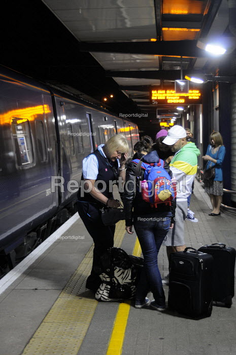 Ashford International Station in Kent: a ticket guard on a late night train into London apologizes to passengers with a child as the train they were travelling on was cancelled, after a relief driver failed to arrive for their changeover shift due to illness. - Stefano Cagnoni - 2012-07-09