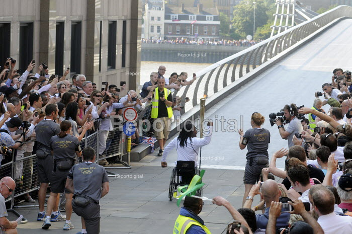 Enthusiastic crowds greet the Olympic Torch Relay as a new torch bearer waves to the crowd prior to setting off across the Millennium Bridge across the River Thames to south London. On the other side another huge crowd can be seen waiting to greet him. - Stefano Cagnoni - 2012-07-26