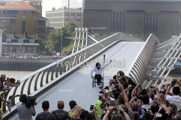 Enthusiastic crowds greet the Olympic Torch Relay as a new torch bearer sets off across the Millennium Bridge across the River Thames to south London. On the other side another huge crowd can be seen waiting to greet him. - Stefano Cagnoni - 2012-07-26