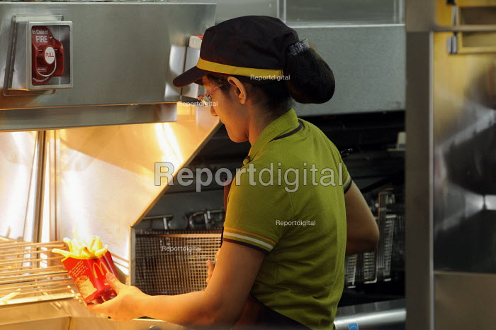 Catering staff dishing up chips at McDonalds inside the Olympic Park in Stratford, one of the major companies sponsoring the London2012 Olympic Games. McDonalds has restricted the market within the Olympic Park to ensure that their company exclusively can serve just chips all other retailers are not allowed to serve chips without an accompanying dish. - Stefano Cagnoni - 2012-07-26