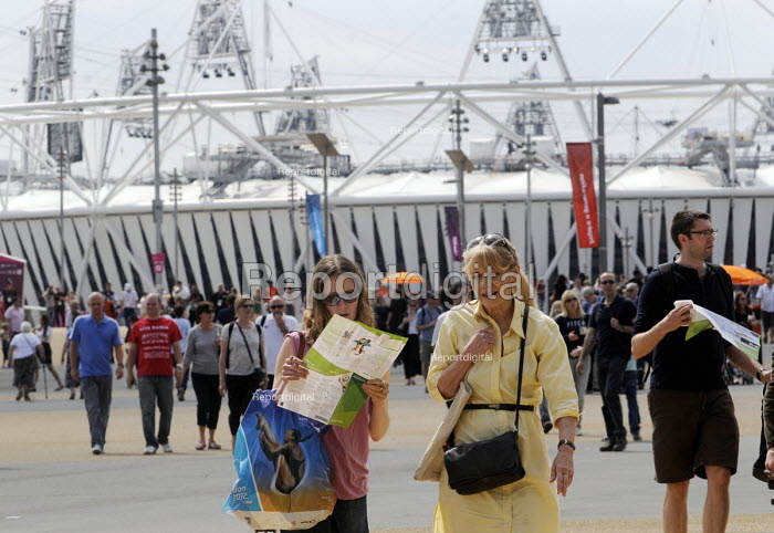 Women examine their map as they enter the Olympic Park in Stratford on the first competitve day of the London2012 Olympic Games, with the Olympic Stadium behind them. - Stefano Cagnoni - 2012-07-28