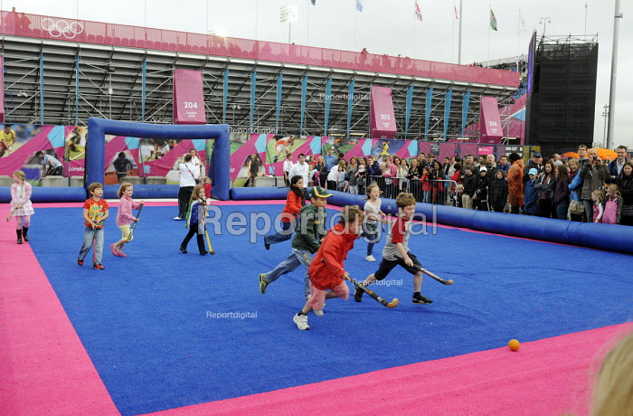Children play hockey outside the Riverside Arena in the Olympic Park in Stratford at the London 2012 Olympic Games during a break from watching Olympic athletes compete in their own qualifying matches. - Stefano Cagnoni - 2012-07-31