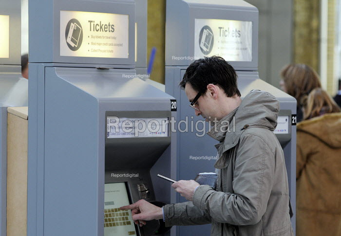 Commuters at the newly opened concourse at King's Cross Station. Passenger using his iPhone to key in his reference to collect his pre-paid ticket from the automated ticket machine. - Stefano Cagnoni - 2012-03-19