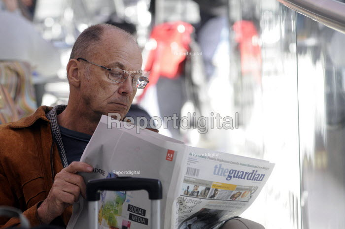 Man reading a copy of The Guardian whilst waiting for a train at King's Cross Station. - Stefano Cagnoni - 2012-03-19