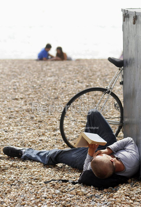 Man reading a book whilst lying on the beach at Brighton. - Stefano Cagnoni - 2012-09-10