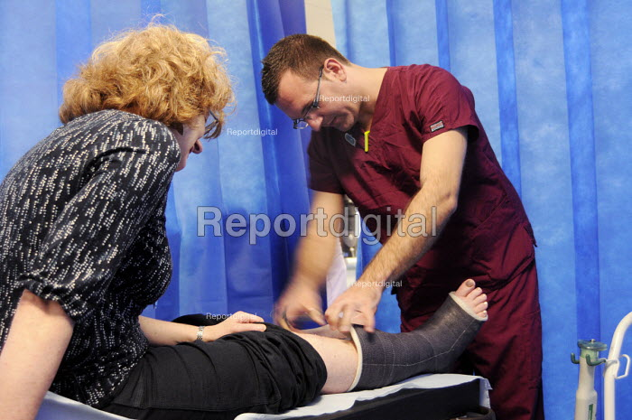 Male nurse using a cutting tool to remove the plaster from a woman with a broken leg in the Fracture Clinic at University College Hospital in London. - Stefano Cagnoni - 2012-08-29