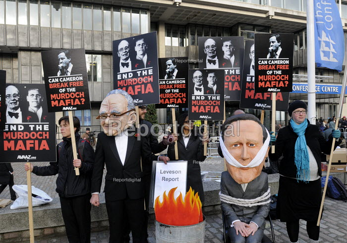 Members of the AVAAZ pressure group protest against press monopoly and power as the Leveson Report into press ethics and practise is published in a press conference at the QEII Centre in London behind them. - Stefano Cagnoni - 2012-11-29