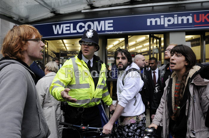 Policeman remonstrating with local community activists protesting at the MIPIM property fair held at Olympia, in protest at lack of affordable housing in the UK and especially in London. - Stefano Cagnoni - 2014-10-15