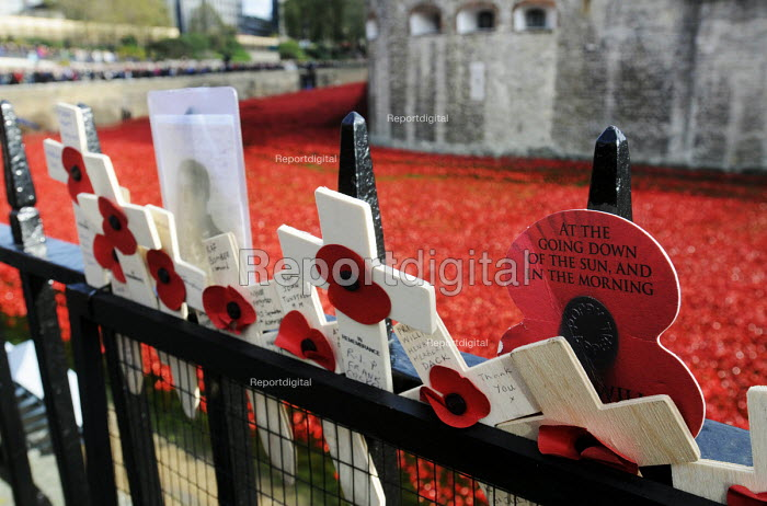 Armistice Day on the 100th Anniversary of the year in which the First World War began. Poppies and crosses are laid by the public to remember the war dead on the gates of the Tower of London; all around them in the Tower moat lie the 888,246 ceramic poppies, the completed art installation by Paul Cummins, representing each life lost of a British or colonial soldier who died fighting in the Great War - Stefano Cagnoni - 2014-11-11