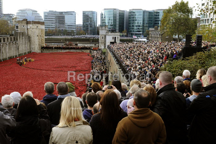 Two Minute Silence to remember the war dead on Armistice Day on the 100th Anniversary of the year in which the First World War began. In the moat at the Tower of London lie 888,246 ceramic poppies, the completed art installation by Paul Cummins, representing each life lost of a British or colonial soldier who died fighting in the Great War - Stefano Cagnoni - 2014-11-11
