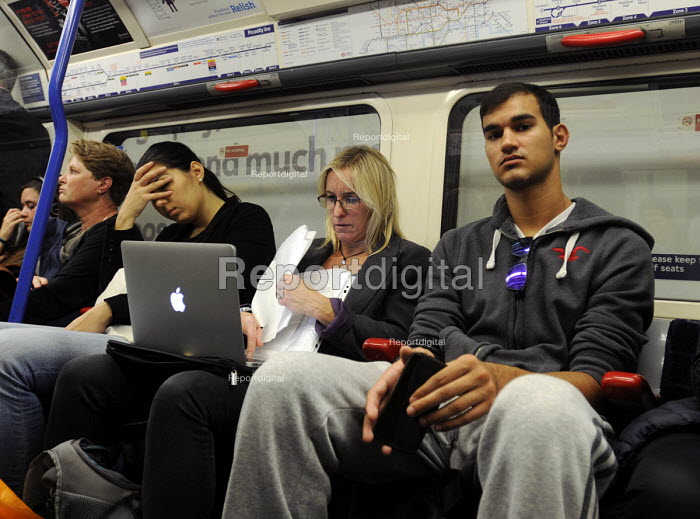 Woman working on her Apple laptop as she travels on the London underground. - Stefano Cagnoni - 2014-09-24