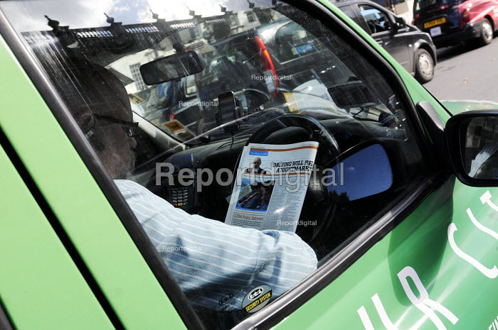 Driver in his car reading an article entitled 'Driving Will Be A Nightmare' whilst stuck in a traffic jam in Westminster, London. - Stefano Cagnoni - 2014-09-24