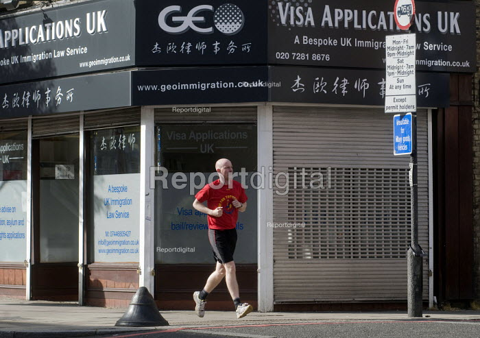 Male jogger passing offices advertising its legal advice for Visa Applications, immigration, asylum and human rights issues, Holloway, north London. - Stefano Cagnoni - 2015-05-07