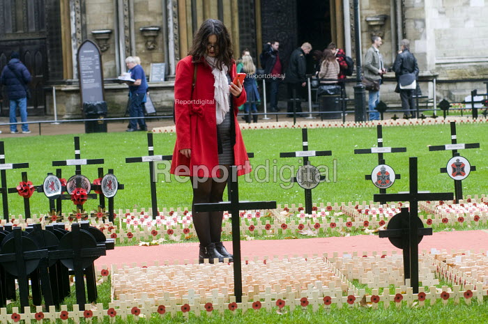 Young woman in red coat, carrying a red mobile phone, looks at the wooden crosses with poppies commemorating the dead of World War One, planted in the Royal Legion Field of Remembrance, Westminster, 2015. - Stefano Cagnoni - 2015-11-04