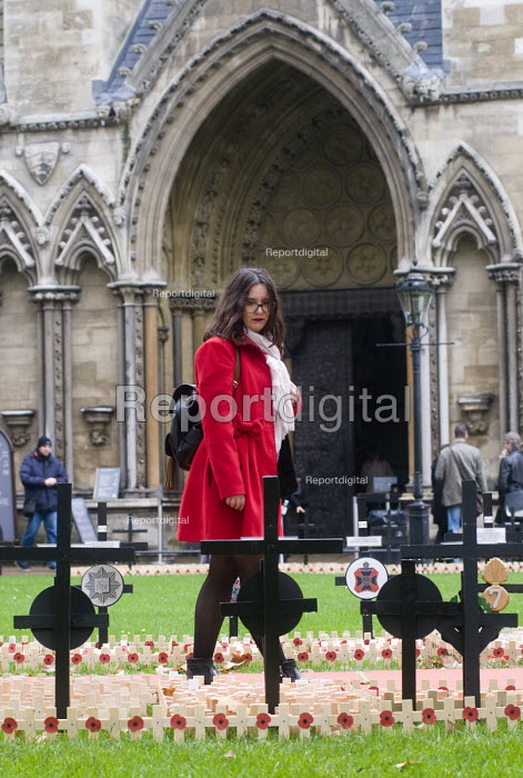 Young woman in red coat looks at the wooden crosses with poppies commemorating the dead of World War One, planted in the Royal Legion Field of Remembrance, Westminster, 2015. - Stefano Cagnoni - 2015-11-04