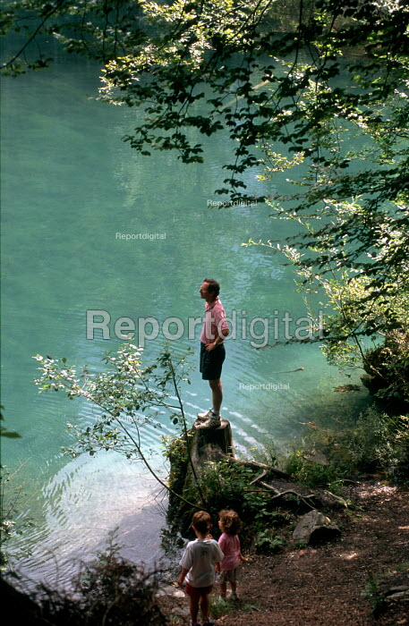 Man enjoying the peace of a lake as children look on - Stefano Cagnoni - 1997-08-25