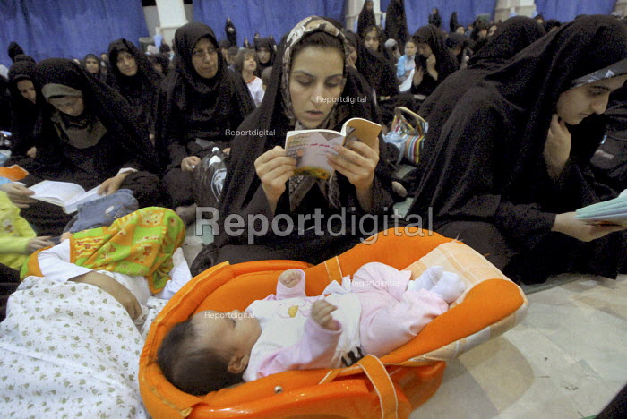 An Iranian female reads holy Koran during a religious ceremony to mark the anniversary of the death of the first Shi'ite Muslim, Imam al-Ali, at a grand mosque in Tehran, Iran.